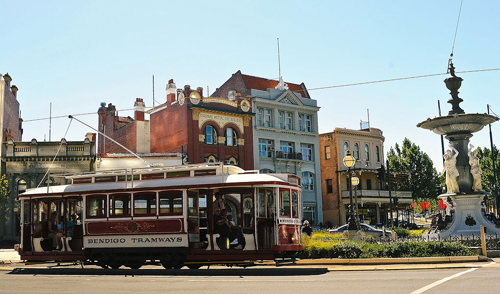 Tram full of passengers passing historic buildings in Bendigo