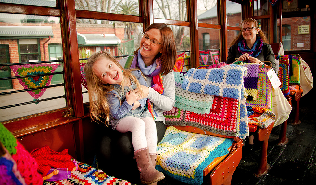 Young family laughing aboard the Yarn Bomb Tram in Bendigo
