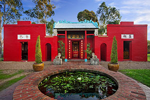 Bright red Bendigo Joss House Temple exterior with fish pond