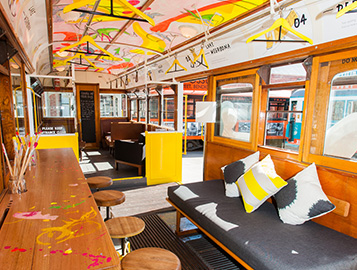 Internal Fit Out of the Schaller Tram featuring a desk, day bed and hand painted artwork on ceiling