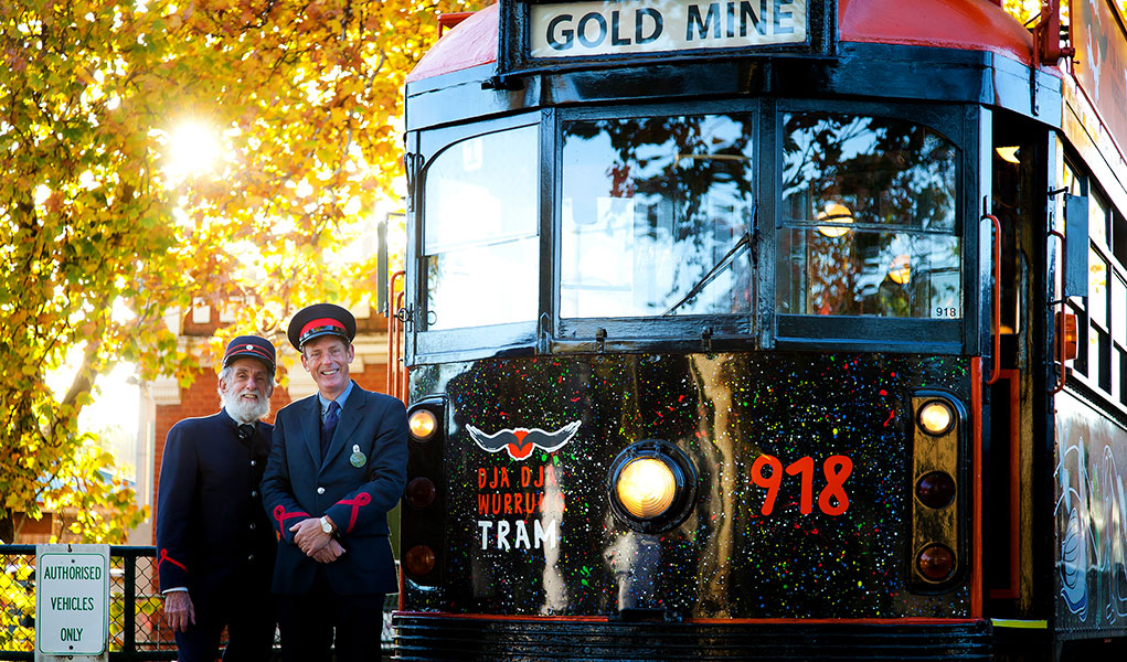 Two Tram Drivers standing in front of the Dja Dja Wurrung Tram with Autumn Leaves in the background