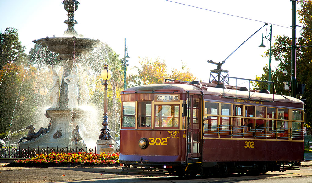 Burgundy heritage tram sitting in front of fountain
